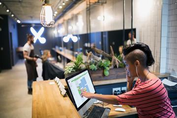 Hipster hairstylist working front desk computer hair salon