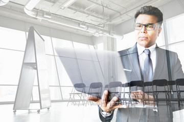 Digital composite businessman working at laptop conference room