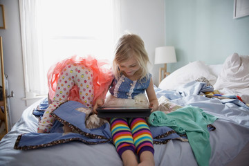 Sisters playing and using digital tablet on bed