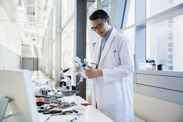 Engineer in lab coat assembling robot