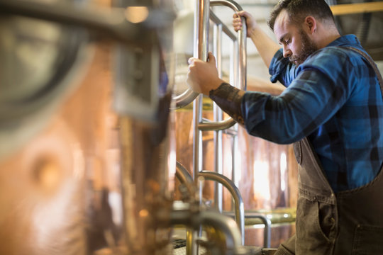 Brewery worker checking copper stills