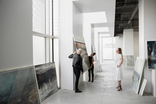 Art dealers hanging painting on gallery wall