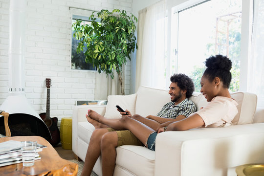 Casual couple relaxing watching TV in living room