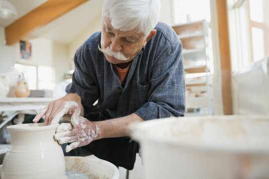 Man throwing clay on potters wheel