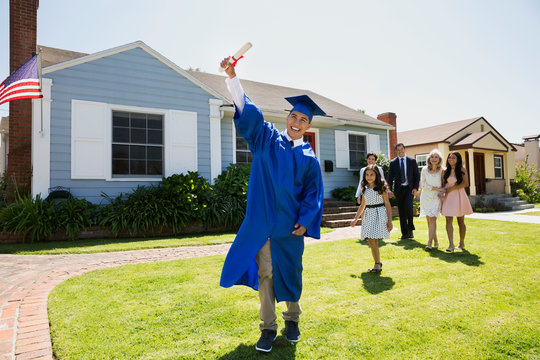 Exuberant graduate holding diploma with family front yard