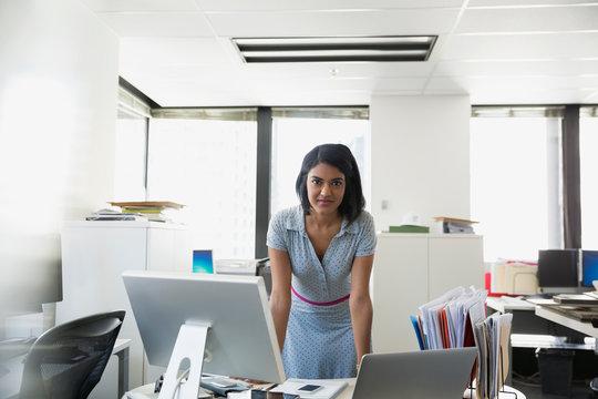 Portrait confident businesswoman leaning on office desk