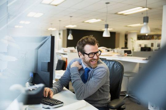 Smiling businessman working at computer looking over shoulder