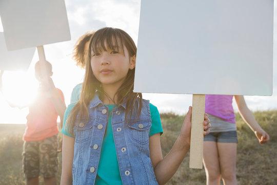 Portrait of cute girl holding blank billboard during field trip