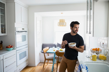 Man eating cereal and looking away in kitchen