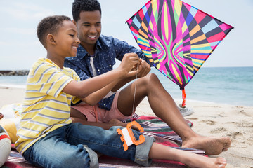 Father and son preparing kite on beach