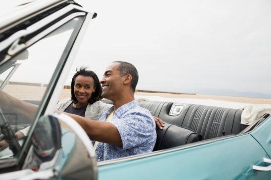 Couple riding in convertible along beach