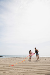 Mother and daughter preparing fly kite sunny beach