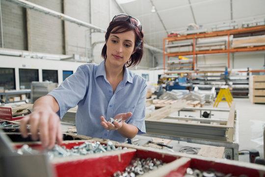 Worker looking through bin of screws in factory