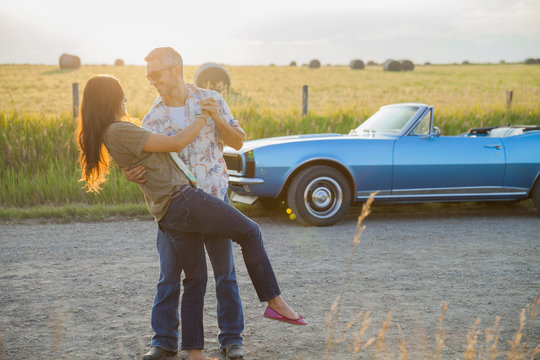 Romantic couple dancing on country road