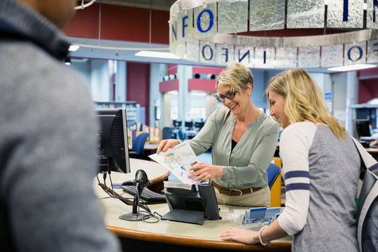 Librarian guiding college student with library map