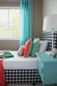 Coral and seafoam green decor on gingham bed