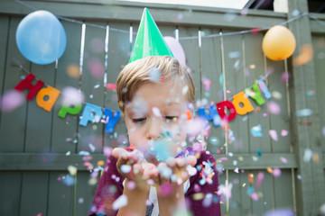 Boy blowing confetti wearing birthday party hat