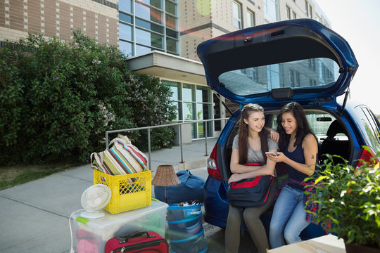 College students texting moving into college dorm