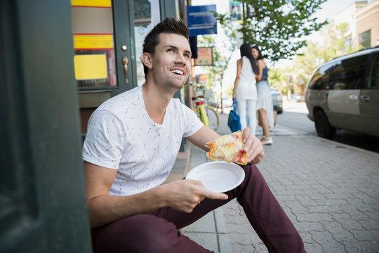 Smiling man eating pizza slice at storefront