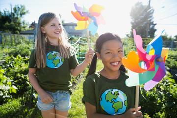 Portrait smiling girls with pinwheels in sunny garden