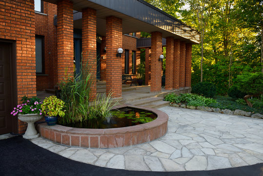 Front entrance with pond and stone veranda on red brick house with pillars