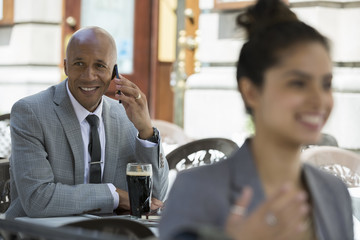 Businessman drinking beer and talking cell phone patio