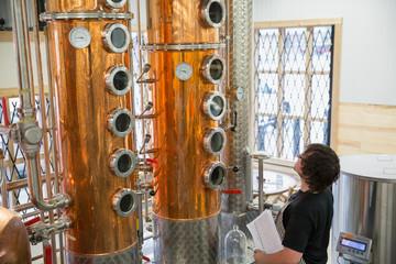 Worker looking up at copper distillery vat