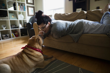 Woman on sofa petting dog's nose in living room