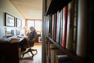 Woman reading book in home office