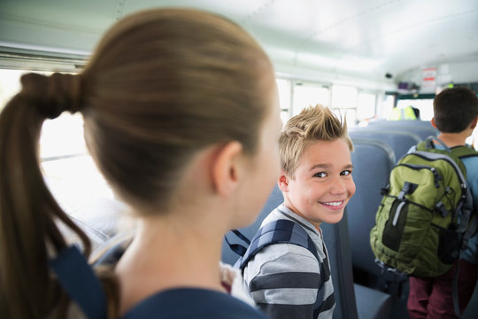 Portrait smiling schoolboy in aisle of school bus