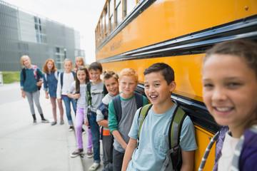 Portrait smiling school kids leaning on school bus