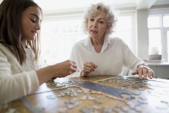 Grandmother and granddaughter assembling jigsaw puzzle dining table