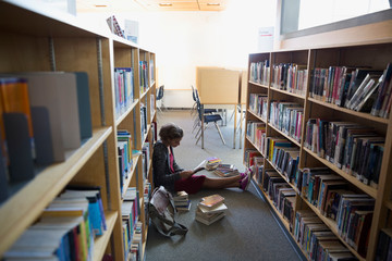 High school student studying on library floor
