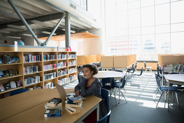 High school student using laptop at table library