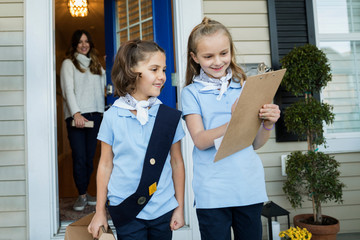 Girl scouts with clipboard selling cookies front stoop