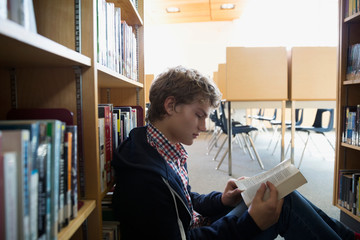 High school student reading book on library floor