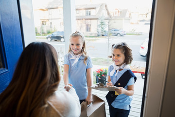 Girl scouts selling cookies woman at front door
