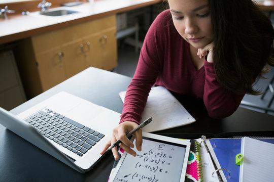 High school student reviewing algebra equations digital tablet