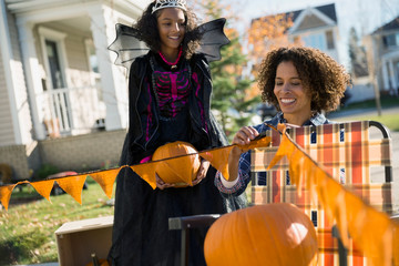 Mother and daughter in Halloween costume decorating yard