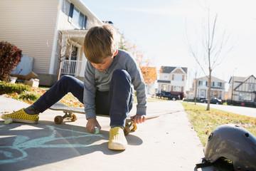 Boy on skateboard drawing on sidewalk with chalk
