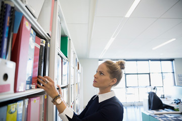 Architect searching for book in office library