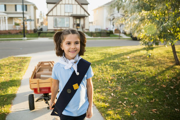 Smiling girl scout with wagon selling cookies neighborhood