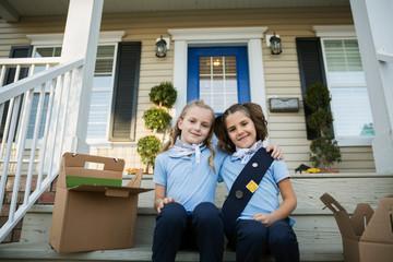 Portrait smiling girl scouts cookies hugging front stoop