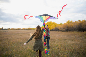 Couple flying a kite in autumn field