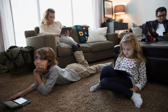 Family relaxing in living room with digital technology