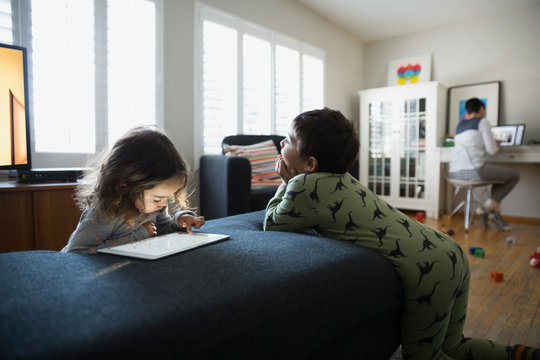 Brother and sister using digital tablet living room