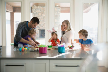 Family coloring Easter eggs in kitchen
