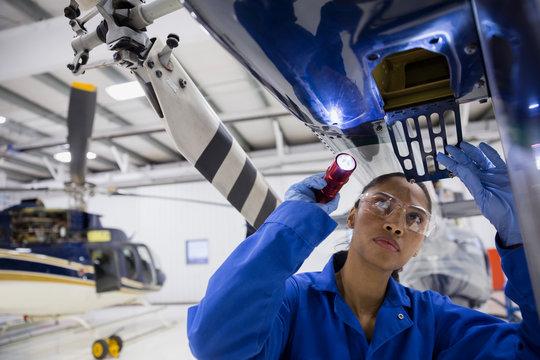 Female helicopter mechanic examining part with flashlight