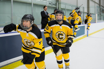 Womens ice hockey team celebrating on ice
