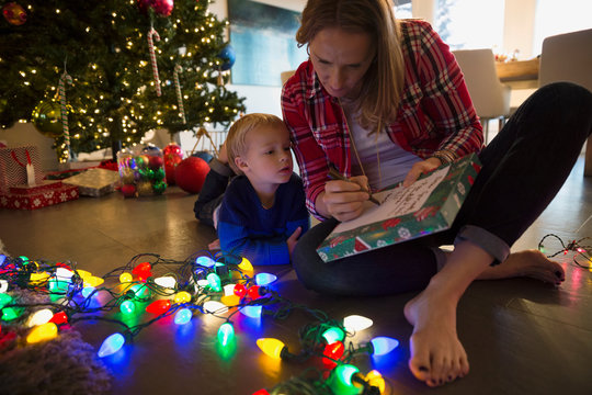 Mother and son making list Christmas string lights